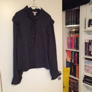 Blus från H&M trend, mörkblå med vita prickar, flertal volanger och vida ärmar om man väljer att knäppa upp knapparna.