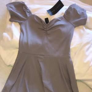 Helt ny och oanvänd klänning i gråaktig färg. Storlek M el. 36/38.