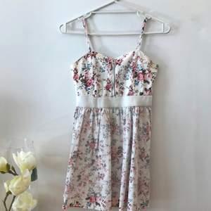 Fin vit klänning med fina blom detaljer som passar den nuvarande värmen!☀️