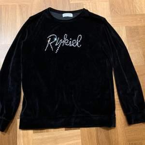 Sammetströja/sweatshirt med glitterstenar från Sonia Rykiel, modellen heter Bertille. Svart. Storlek 152. Sparsamt använd, mkt fint skick. Kvitto/skärmdump från Zalando finns, inköpt jan-19.