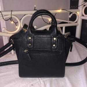 En svart Don Donna väska med axelremmar som går att ta av, 2 ytterfickor och 3 innerfickor. Köpte den för några år sen men endast använd några gånger, väldigt fin men använder den aldrig! Frakt kan diskuteras, behöver väga väskan innan jag kan bestämma ett bra pris på frakt
