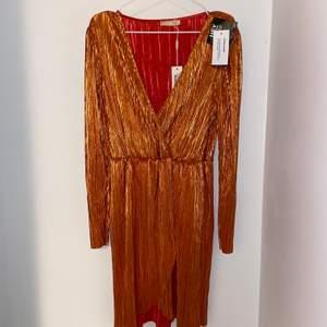"""Oanvänd orange/guldig klänning från """"NLY Eve"""" som fortfarande har lapparna kvar. Orginalpris är 499 kr."""
