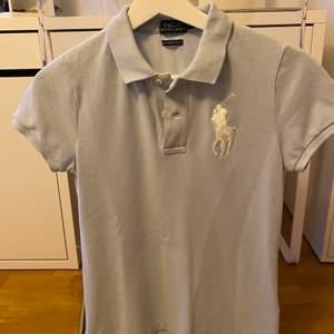 Ljusblå skjorta polo Ralph lauren. Aldrig använd. Vädligt bra kvalite. Fraktkostnad tillkommer