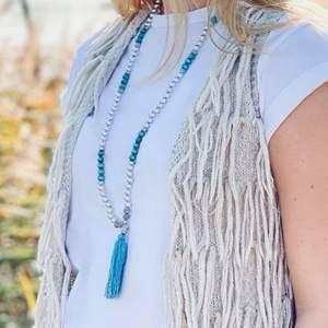 Långt halsband med silver och blått samt blå toffs.