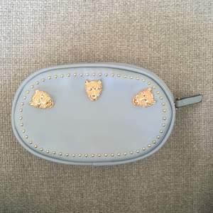 Snygg nitad väska i fakeläder med två fickor inuti. 17,5 x 11 cm stor, 6 cm tjock. Hylsorna baktill går att trä 3cm breda skärp/remmar genom, annars så bra att bära mindre saker i större väska med. Nyskick.