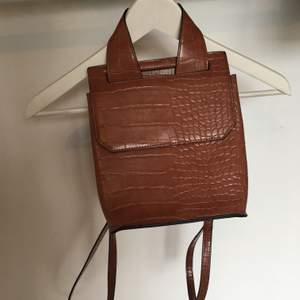En mindre ryggsäck från asos i mycket bra skick med fack inuti, läderimitation.                                                            Möts upp i Sthlm annars står köparen för frakt.