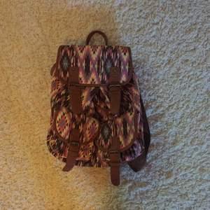 Ryggsäck med färgerna brun, rosa, ljus gul osv. Använd fåtal gånger. Lite sliten vid bandet där man hänger den. Det fixas lätt! Annars fungerar den perfekt. Köparen står för frakten!