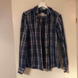 Blårutig skjorta från Peak, är i fint skick och sparsamt använd. Figursydd och normallång i ryggen. Skönt material i bomull, sitter fint på kroppen och väldigt skön!