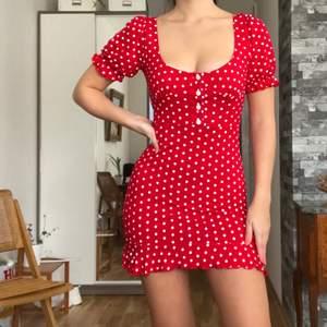 """Oerhört söt & fin """"polka dot"""" klänning i härlig röd färg med små volanger vid ärmarna och klänningkanten. Skönt material & ger kroppen en väldigt snygg form! Går ej upp när man går. Garderoben måste dock rensas och denna får gå. Från Missguided(slutsåld). Originalpris: 359kr. Köpare står för frakt(48kr)! Storlek: XS(passar även S som jag brukar ha, om man inte har problem med att ärmarna sitter lite tight då). Använt en gång. Jag är 168 cm!"""