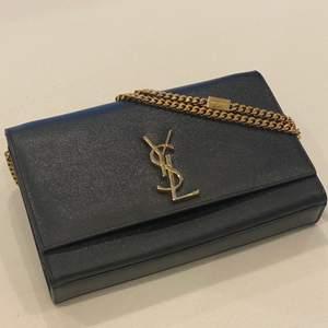 En axelväska väska från Saint Laurent i svart kornigt läder. Väskan stängs med en flap och magnetlås. Framsidan är dekorerad med en stor guldfärgad YSL-logga. Insidan är svart och har en mindre slip-in ficka. På insidan finns en liten fläck men inget som påverkar väskans utseende eller som kan fångas på bild. (Försökte fota den) Väskan bärs i handen eller över axeln med den guldfärgade kedjan. Den kommer med en dustbag och äkthetsbevis! ORD pris ca 15000. Mer information ges på begäran ❤️