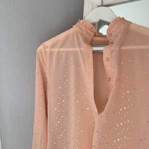 """En blus i storlek 34, färgen är inte rättvis på bilden då den är mer """"peachfärgad"""" i verkligheten, har guldiga prickar vilket gör den lite mer utåtstickande, går både att klä upp den och klä ner den 🥰"""