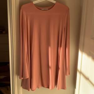 En lös rosa klänning i storlek M. Ärmarna är utvidgade