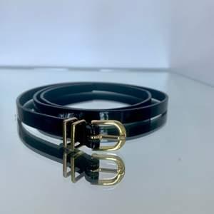 Bälte i blankt läder med guldfärgat spänne. Storlek 85. Fint använt skick. Höjd: 1,2 cm.