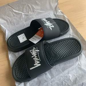 Nike Benassi Stussy Tofflor fabriks nya tofflor oanvända. Vunna på en raffel från Nike Snkrs. Storlek 42,5 EU. Kontakta mig för fler bilder!