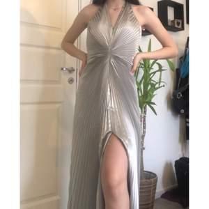 Unik balklänning i silver! Nyskick. Sitter perfekt på mig som är 170cm. Fråga gärna om fler bilder eller mått.