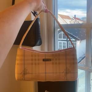 En jätte fin rosa burberry väska finns ej äktaenhets bevis men är skiiit fin till sommaren, rymlig till mobil plånbok nycklar mm.. är ganska sliten med de är de som gör väskan cool priset kan diskuteras
