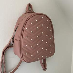 En av väskorna! Rosa med pärlor, liten men gullig.