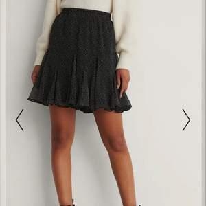 Kjolen är svart med vita prickar med resårband i midjan och väck med volanger nertill. Som är köpt på NA-KD hemsida. Så fin kjol!! Använd fåtal gånger och är i bra skick. Säljer kjolen för att den är för liten. Säljer den för 120kr. På NA-KD hemsidan är kjolen slutsåld!