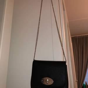 Det är en svart väska med måtten 16cm bredd ➡️, och 15 cm höjd ⬆️. Den är en väska med svart läder och har en silver kedja!💜 Man kan öppna upp sidorna så att den blir större (bild 3)!! Jätte gin väska som passar allt!💕💕