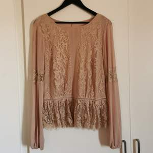 A gorgeous shirt with a lot of lace details, in a nude color. Sits just right over the bust and not tight around the arms. Has a little of a pemplum effect when on.