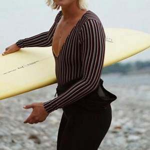 """Oanvänd svart randig baddräkt/body med öppen rygg och djup urringning. Såhär står det om den på Billabongs hemsida: """" Designed to stay put in the surf with UPF 50+ sun protection, the long sleeve swimsuit features an exposed back and deep V neck cut. The womens surf suit offers a slim cut seat with a """"Biarritz"""" cut."""" Säljes pga köpt fel storlek. Lånade bilder"""