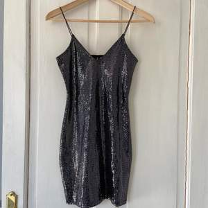 En fin ganska basic miniklänning som går till lite under rumpan. Helsvart men små paljetter över hela, har spagetti band och sitter tight 💓 använd en gång så den är som ny