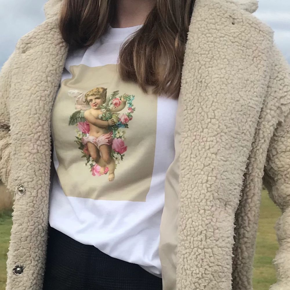 Vit T-shirt med tryck. Storlek small. Skönt och luftigt tyg. Knappt använd alls. Trycket består av en ängel med rosa blommor och beige bakgrund 💛. T-shirts.