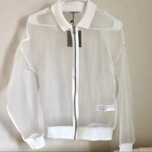 Säljer denna coola genomskinliga/vita bomberjackan från Zara. Superfin skimmrig mesh typ med vit krage, fin med typ en klänning eller linne under på sommaren. Nyskick (men lappen är inte kvar längre). Stl M