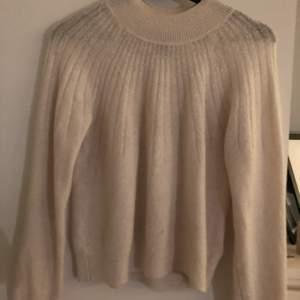 En vit stickad tröja men instickande ränder. En fin markerad krage med skönt material. Tröjan är i storlek XS men passar mig med storlek S. Köpt från Lindex och använd några gånger.