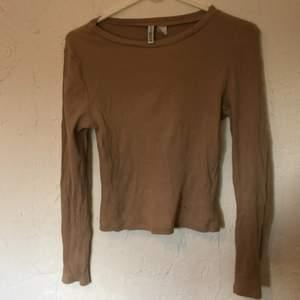 Beige ribbad långärmad tröja med tunt och stretchigt tyg. 93% bomull. 7% elastan. H&M basic Divided. Litet hål på framsida, mindre än en halv cm i diameter.