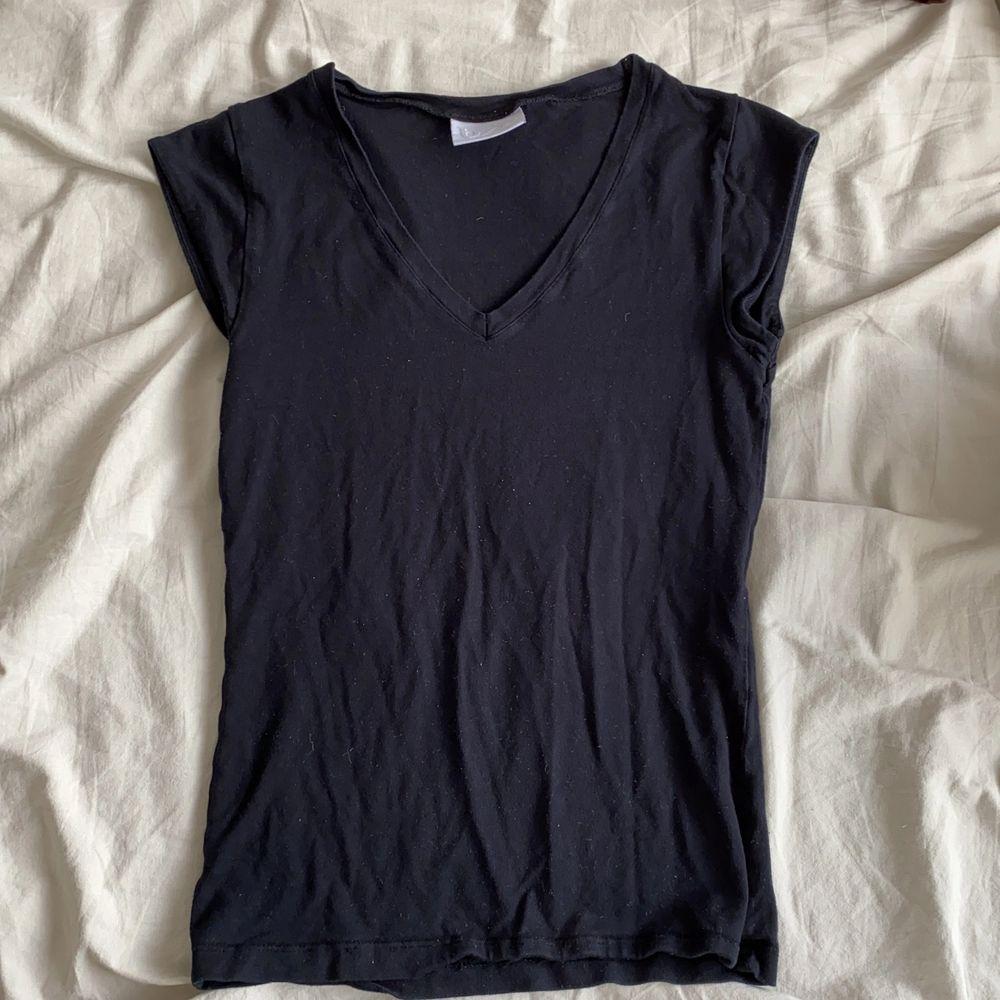 Svart T-shirt med snygg urringning!. T-shirts.
