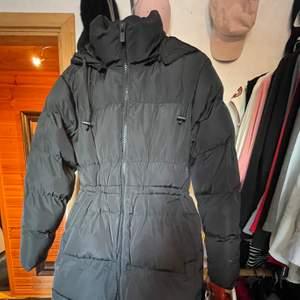 Helt ny, aldrig använd. Lång svart jacka med luva, dragsko i midjan. Mycket fin och varm!