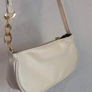 En krämig vit väska med fina gulddetaljer som lätt passar med alla dina outfits. Den är helt oanvänd och köpt för en månad sen. Köpte den för 150 och säljer den för 100. Köparen står för frakten. Skriv gärna om du vill att jag skickar fler bilder🥰