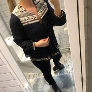 En svart kofta/tröja/jacka vad man vill använda den som med mönsterdetalj och knytband i fram med toffsar nedtill. Använd endast fåtal gånger. Tunt material som faller fint.