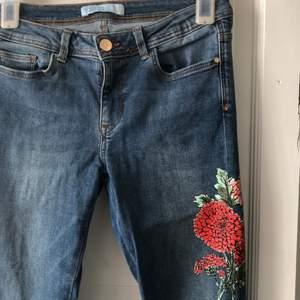 Snygga stretch jeans med Blomdetaljer från Zara. Rå kant nertill. Snygg vår/sommar byxa! Använd fåtal gånger, och i fint skick!