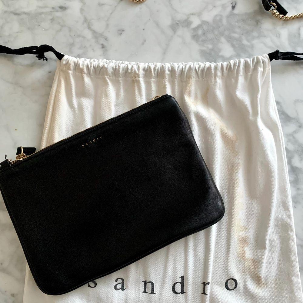 Väska i läder med avtagbar rem från Sandro Paris. Aldrig använd. Medföljande dustbag. Bredd 24: cm, höjd: 17 cm. Nypris cirka 1600 kr.. Accessoarer.