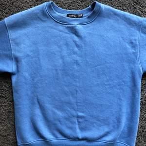 Skön sweatshirt från Boohoo i en behaglig blå färg. Tröjans innematerial är filt, vilket ger en skön känsla. Fint skick! Frakt tillkommer.