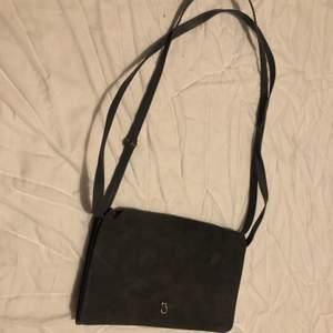 Super fin grå crossbody väska med justerbar axelrem, kan också användas som en axelväska. Äkta läder och mocka med två fack inuti!
