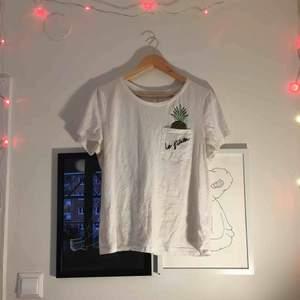 Jätteskön vit t-shirt från H&M med en charmig ananas som sticker upp ur bröstfickan🍍