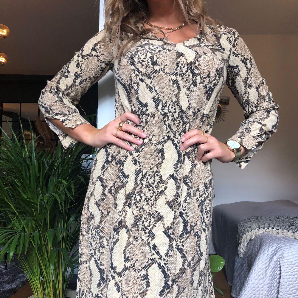 Midilång klänning med slits, långa ärmar och omlottopp. Storlek 34. Frakt 55 kr tillkommer.. Klänningar.