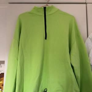 En neon grön sweatshirt med dragkedja och justerbar midja. Helt oanvänd. Köpt i New York. Frakt tillkommer. Priset är förhandlingsbart.