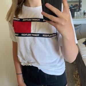 Vit T-shirt från Tommy hilfiger. Den har två små fläckar med den stan inte när man stoppar in tröjan. Den är sådär stor i storlek. Högst bud får den (pris+frakt)