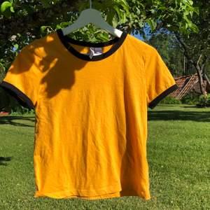 En gul t-shirt med svart runt nacke/armar. Skulle säga att storleken är mer utav en XS än en S, men det beror på hur man vill att den ska sitta😆 säljer då den inte längre passar☺️ pris kan självklart diskuteras! Köpare betalar frakt📦 kan samfrakta!🥰