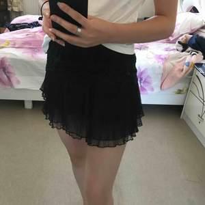 En jättesöt svart kjol med volanger med inbyggda shorts Bra skick, 120+frakt