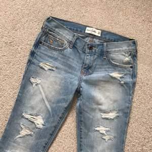 Abercrombie jeans med slitningar på benen. Strl. 14, vilket motsvarar W. 23/24. Helt nya, aldrig använda. Lågmidjade.
