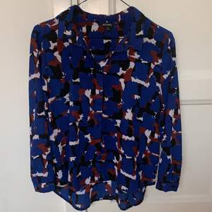 Hel och fin mönstrad blus i färgerna blå, vit, lila och svart. Använd sparsamt. Storlek M men skulle snarare säga S/XS.