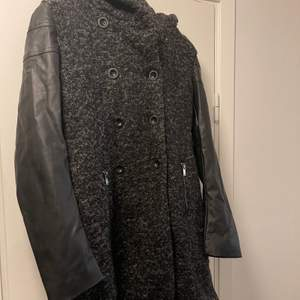 En grå/svart kappa med en stor liva och läderimitations ärmar