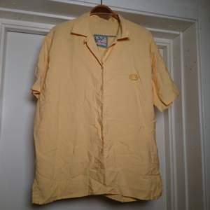 Kortärmad vintageskjorta i fin gul färg! Inte i nyskick men hel och fin. Ingen storleksmärkning men bedömmer den som en L🌼