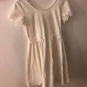 En vit klänning från La Redoute i storlek 32/34 vilket motsvarat ca XS. Den har blommigt spetsmönster på ärmarna och runt midjan. Knappt använd.