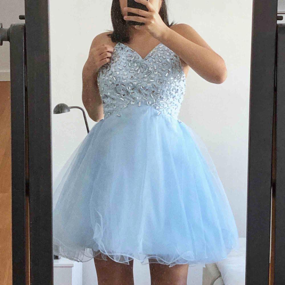 En fantastiskt fin klänning jag beställde för länge sen till balen. Använde dock aldrig den, så den är i nyskick. Kors i ryggen och stenar på framsidan. Kjolen är av tyll. (Frakt tillkommer om den ska skickas). Klänningar.